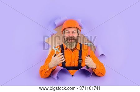 Advertising. Repairman. Through Paper. Bearded Builder Look Through Paper. Bearded Man With Repair T