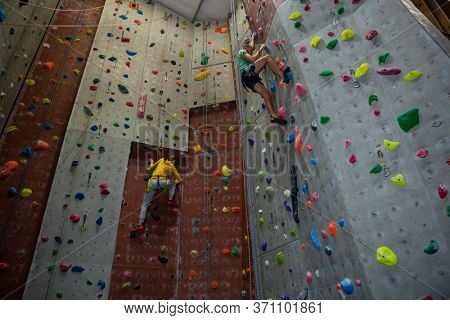Low angle view of athletes practicing rock climbing in health club