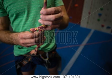 Midsection of male athlete tying rope while standing in health club