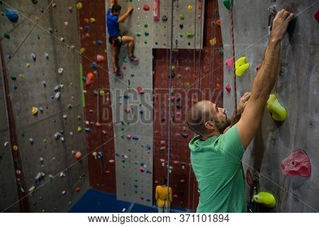 Confident male athelets climbing wall in club