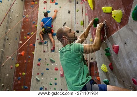 Fit athletes climbing wall in health club