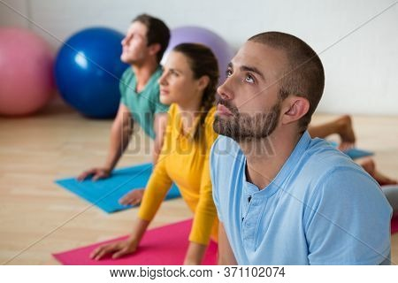 Yoga instructor guiding students in practicing cobra pose at health club