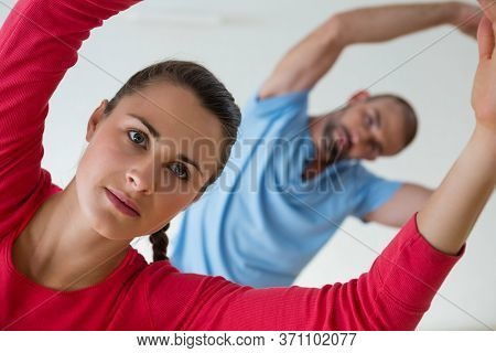 Female student with male instructor exercising in health club