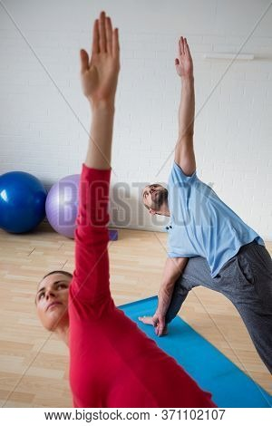 Male Instructor with female student practicing triange pose in yoga studio
