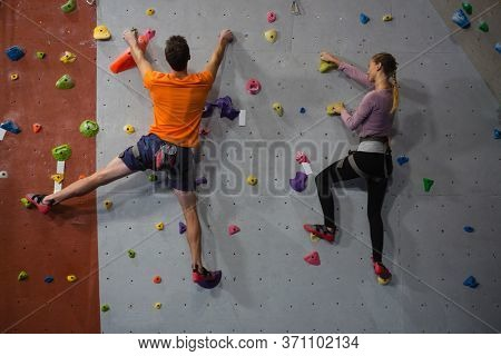 Rear view of athletes rock climbing in health club