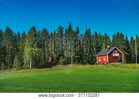Summer Panoramic View Of Agricultural Green Grass Meadow Field, Norwegian Red House In Scandinavian