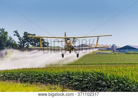 A crop duster applies chemicals to a field of vegetation.