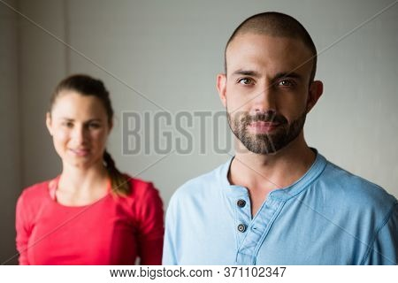 Portrait of yoga instructor with student standing in yoga studio