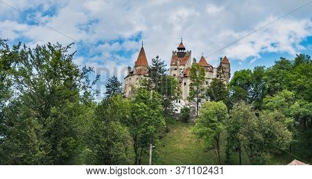 Bran Or Dracula Castle Under Blue Cloudy Sky, Panoramic View From Bran Village In Transylvania, Roma