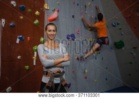 Portrait of confident athlete standing against man climbing wall in health club