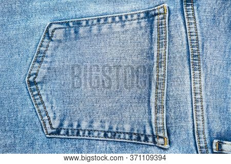 Close-up Pocket Of Denim Blue Fabric With Yellow Seams. Fashionable Rough Jeans