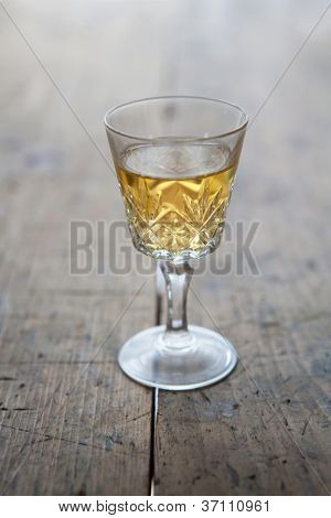 Glass of white wine in a antique glass, placed on a old wooden table.