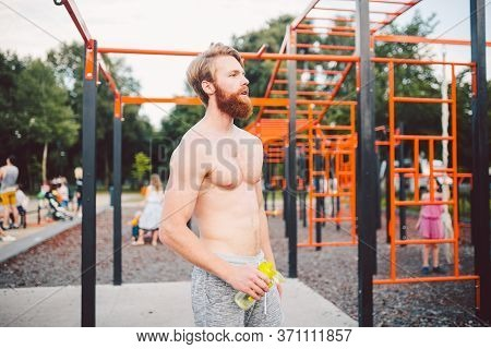 Athlete Relaxing After Intense Workout, Drinking Water. Young Strong Sportsman Male Drinking Water F
