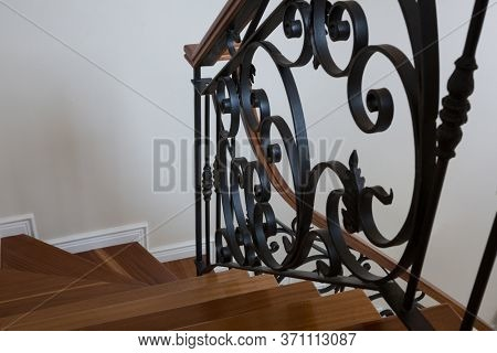 Interior wooden stairs with metal railing at home