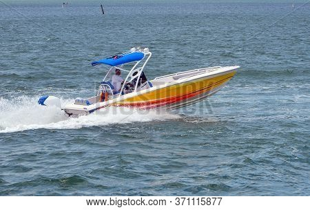 A Colorful Motorboat Yellow With Orange Trim And A Blue Canvas Canopy Speeding On The Florida Intrac