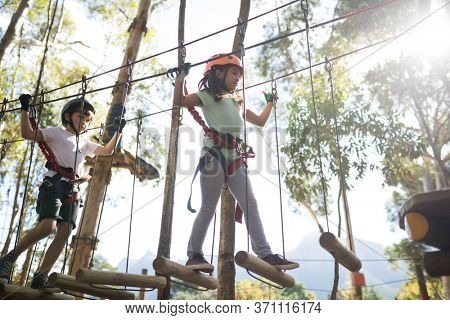 Determined kids crossing zip line on a sunny day