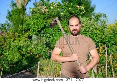 An Adult Male Farmer With A Hoe Posing In The The Farm. High Quality Photo