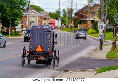 Amish Buggy Travels Through Village