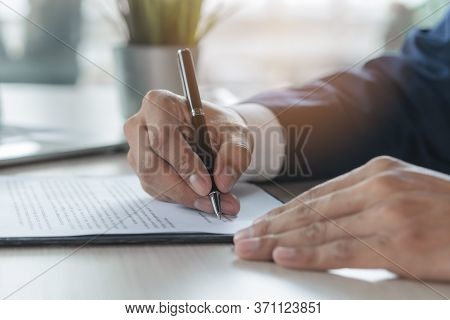 Contract Document Official. Close Up Person Signing His Signature To Agreement Document To Guarantee