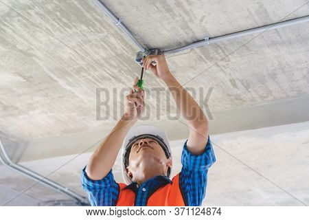 Construction Worker And Contractor. Electrician Prepare To Wire Electric System On The Ceiling In Re