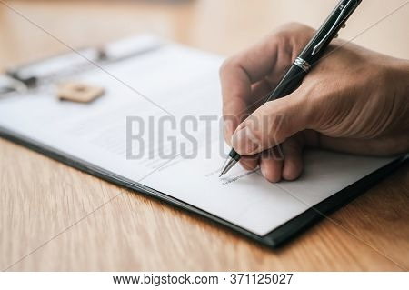Close Up Hand Of Person Signing Signature To Contract Document On The Table With Bank