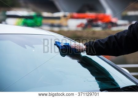 Hand Cleaning A Car's Windshield With A Micro Fiber Cloth. Washing Vehicle Front Windshield Glass.