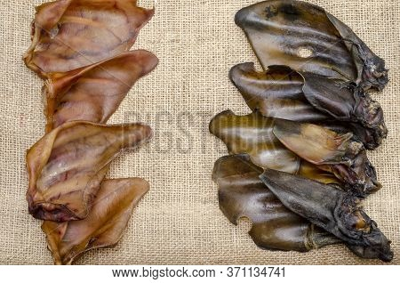 A Group Of Dried Pork And Beef Ears On Burlap. Natural Chewing Treats For Dogs. Production And Trade
