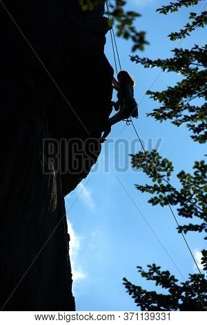 Brave Lady Mountaineer Climbing Extremely Vertical Rock Under Beautiful Blue Sky. Young Woman Climbe