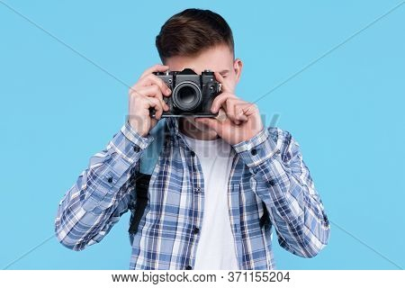 Young Man Photographer In White T-shirt, Checkered Shirt, Is Holding Retro Photo Camera, Standing On