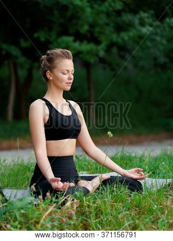 Profile Portrait Of A Young Woman In Black Sportwear Seated On A Yoga Mat With Closed Eyes In Positi