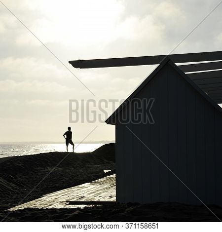 Silhouette Of A Guy On A Sunset Background On A Beach In Evening.   The Boy Silhouette On The Beach