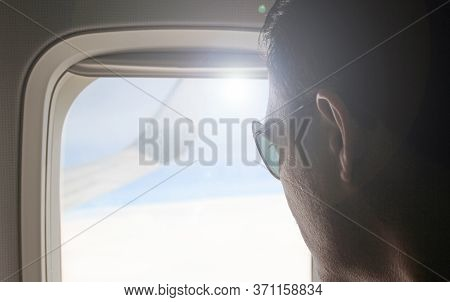 Young Passenger Looking Out Through Window Of The Flying Airplane. Side View Of Handsome Man Against