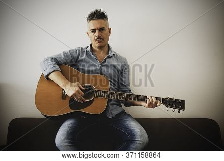 Handsome Man In Casual Clothes Is Posing With His Acoustic Guitar. Guy Playing Guitar Sitting On Sof