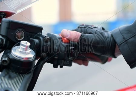 The Biker Puts His Hand On The Gas Handle On The Motorcycle, Turns On The Ignition And Starts The Mo