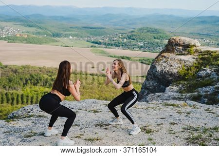Two Girls Play Sports Keeping Their Distance. Playing Sports In The Mountains. Sports In Quarantine.