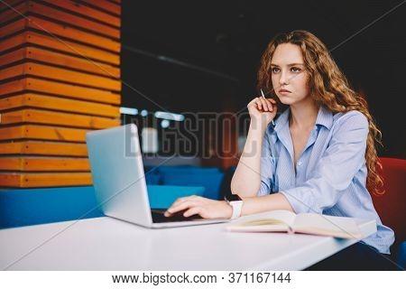 Pondering Cute Graphic Designer Working On Freelance Using Laptop Computer