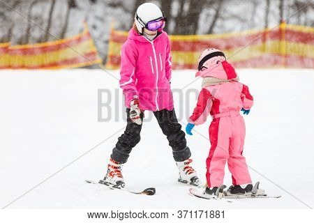 Mother And Little Child Skiing In Alps Mountains. Active Mom And Kid With Safety Helmet, Goggles And