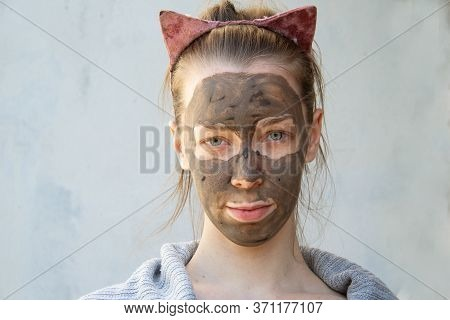 A Light-skinned Young Woman Put A Clay Mask On Her Face With Freckles. It Stands Near A Heterogeneou