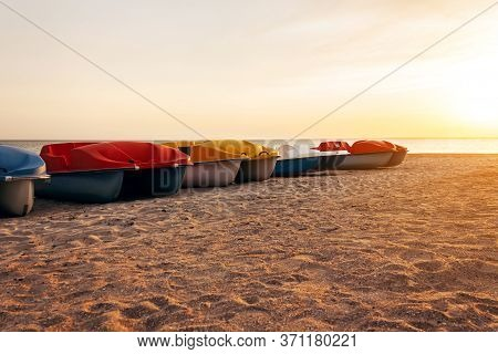 Pedal Boats On The Sunset On A Tropical Island Beach. Colorful Catamaran On An Empty Sea Shore On Ev