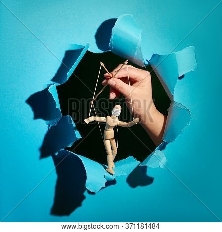 Sinister Hand Of Puppet Master Controlling Dummy Puppet With Flu Face Mask In Paper Hole. Coronaviru