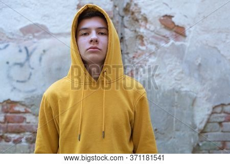 A Teenager In A Yellow Hoody Arrogantly Looks At The Camera, Against The Background Of A Decrepit Wa