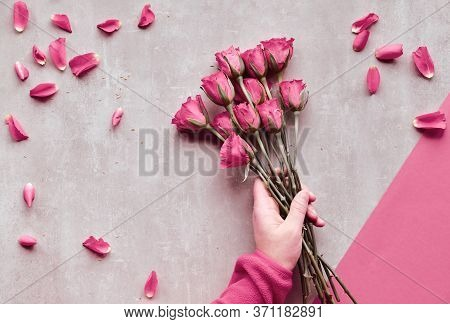 Diagonal Geometric Paper Background On Stone. Flat Lay, Female Hands Holding Pink Roses, Scattered P