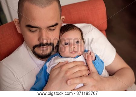 Father Sleeping In Armchair While Holding Infant Daughter. Baby Is Awake And Looking At Camera With