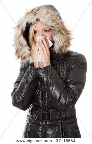 Young woman wearing furry hood, sneezes during cold day. Woman is holding tissue next to her nose.
