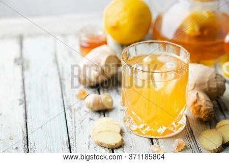 Yellow Drink With Ginger, Lemon And Ice In A Glass, Refreshing Homemade Ginger Lemonade Or Ale On Wh