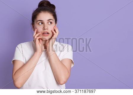 Beautiful Female With Hair Bun Looking Aside With Astonished Facial Expression, Touching Her Cheeks