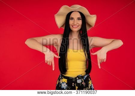 Atractive Girl On Summer Vacation Surprised And Pointing Finger On Copy Space Isolated Over Red Back