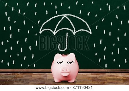 Saving For A Rainy Day With Pink Piggy Bank In Classroom With Chalkboard Illustration Of Umbrella Sh