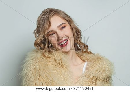 Portrait Of Smiling Woman In Eco Friendly Faux Fur Coat On White Background