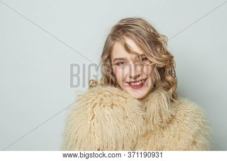 Portrait Of Happy Woman In Eco Friendly Faux Fur Coat On White Background